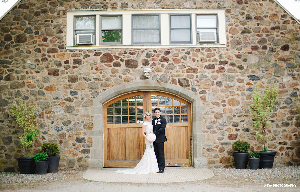 Bride and Groom in front of stone building at Radnor Hunt